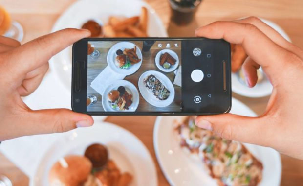 person using phone to take photo of food