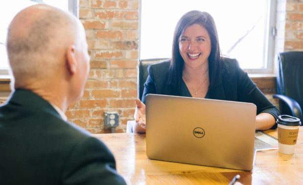 office worker smiling with open laptop