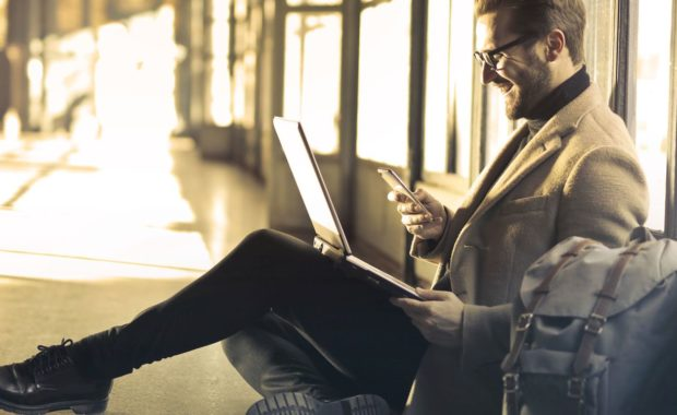 Man reading laptop and phone